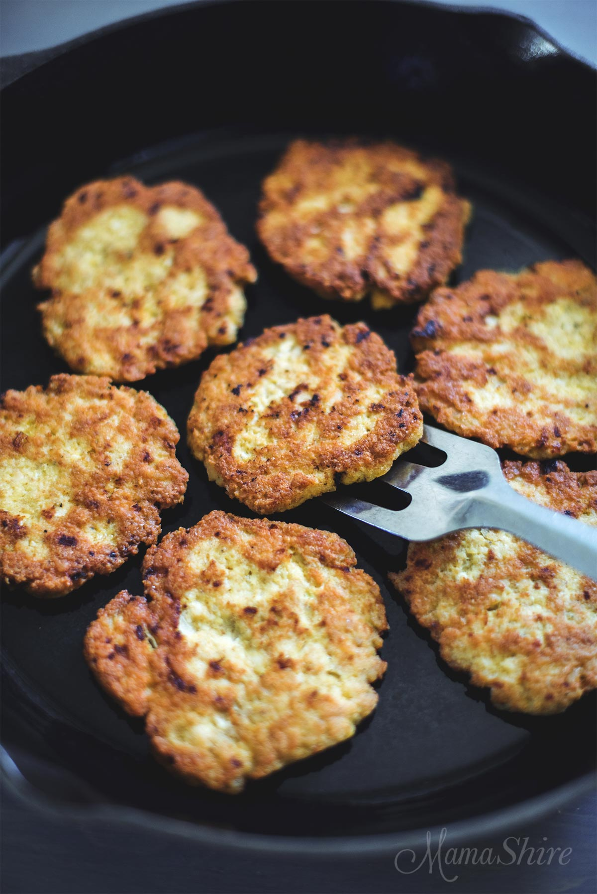 Several chicken patties in an iron skillet that were made with a homemade chicken patties recipe that is gluten-free.