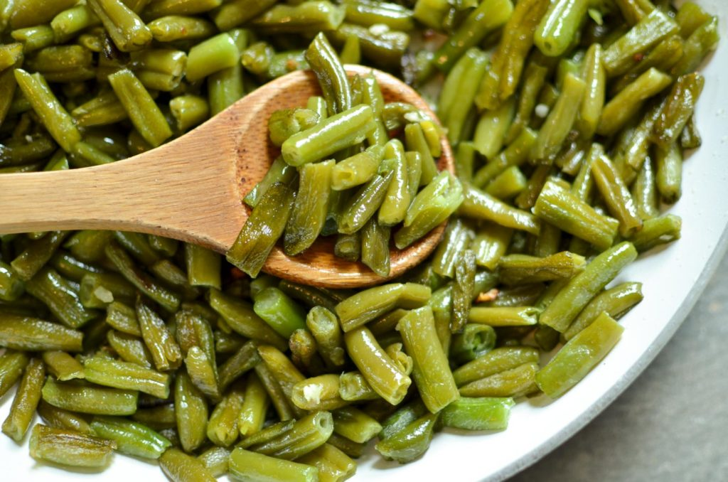 A pan of fried green beans with a wooden spoon.