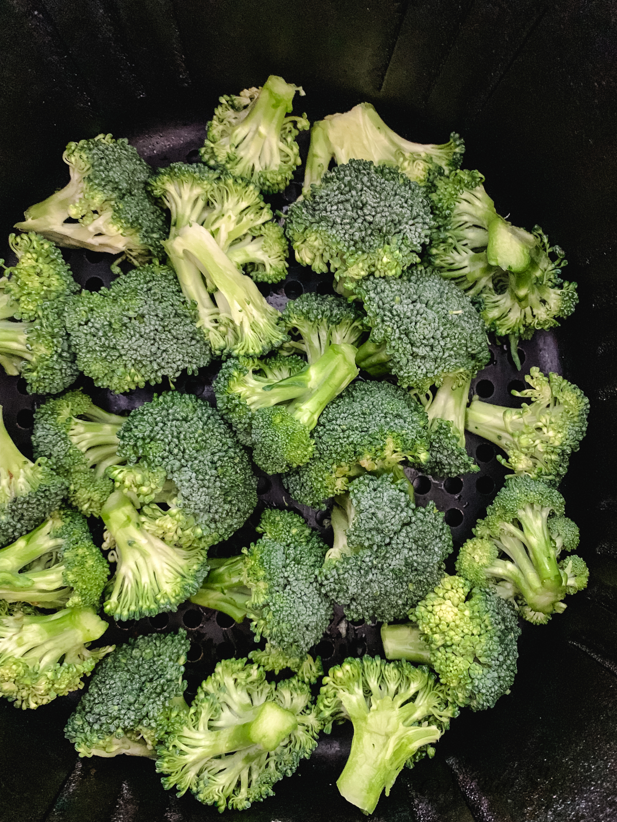 Broccoli in the air fryer basket.