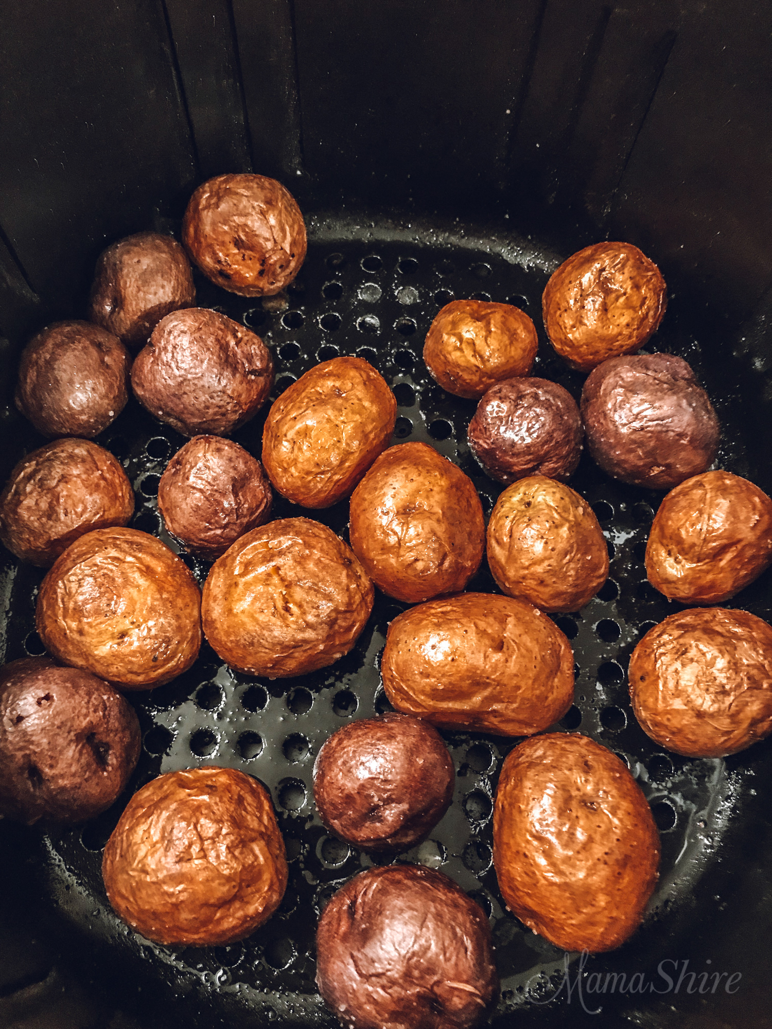 Baby potatoes in the basket of an air fryer.