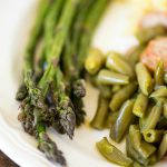 Air fryer asparagus served with green beans and sausage.