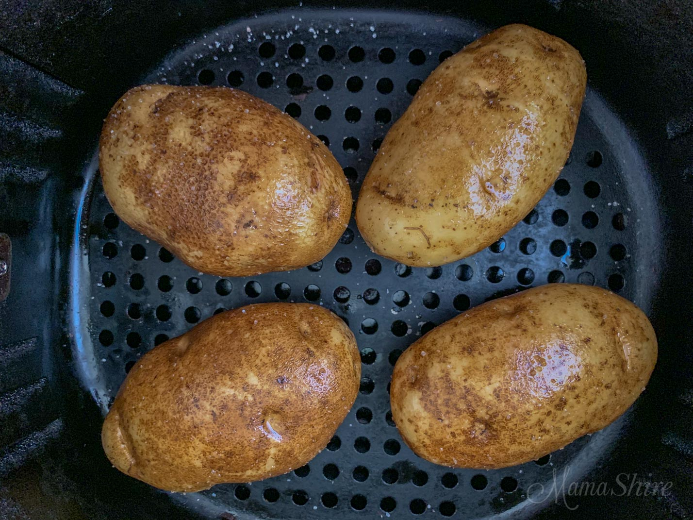 Air fryer basket with potatoes.