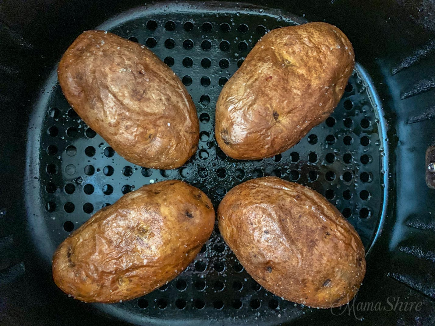 Baked Potatoes in an air fryer basket.