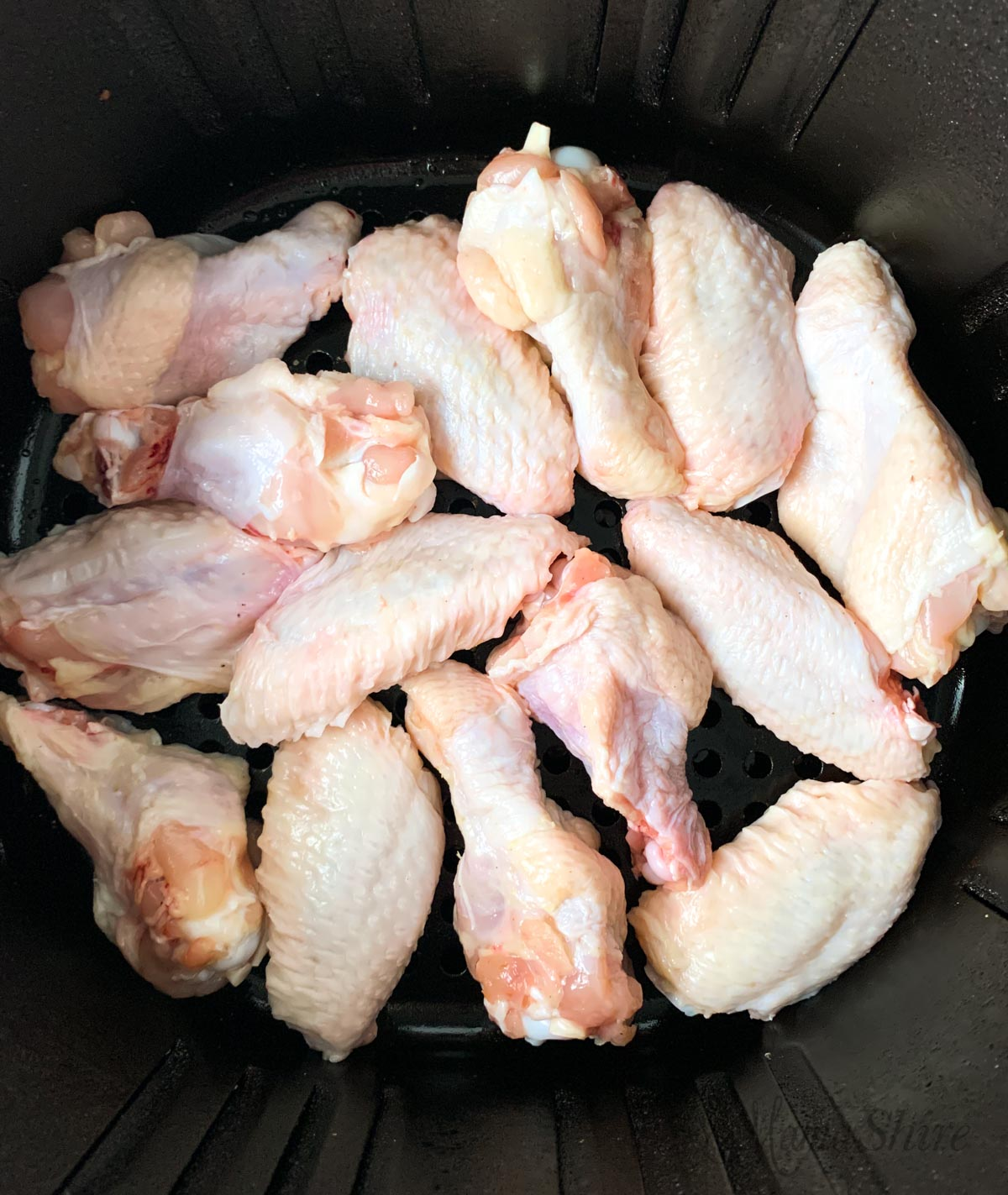 Chicken wings in an air fryer ready to cook.