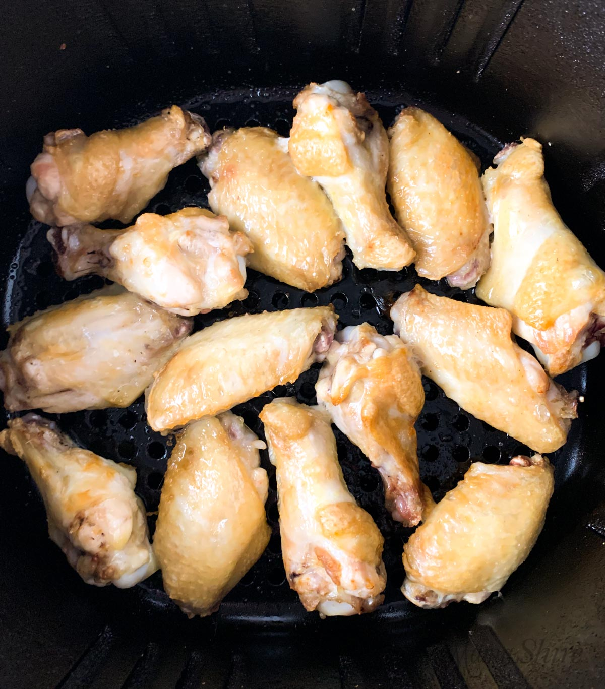 Chicken wings halfway cooked in an air fryer.