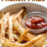 Air fryer french fries with a little bowl of ketchup served on the side.