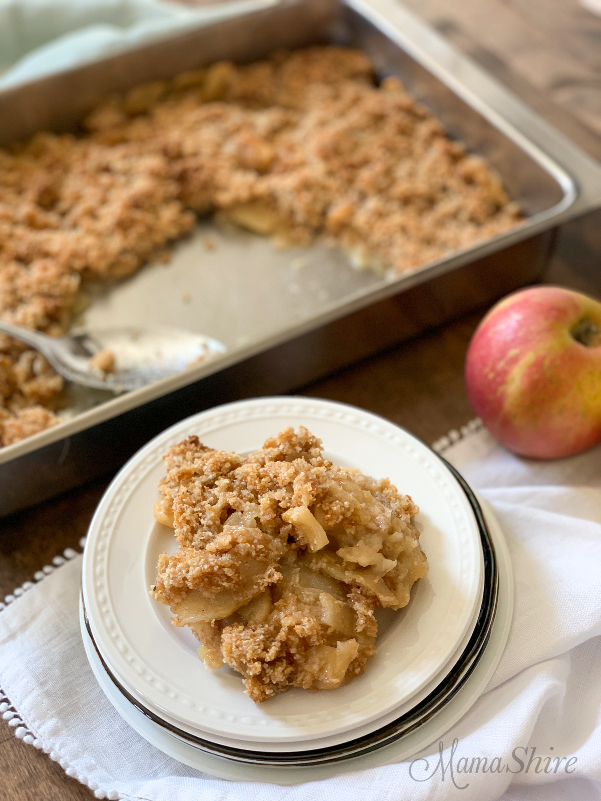 Grain-free apple crisp on a dessert plate with the whole pan and an apple.