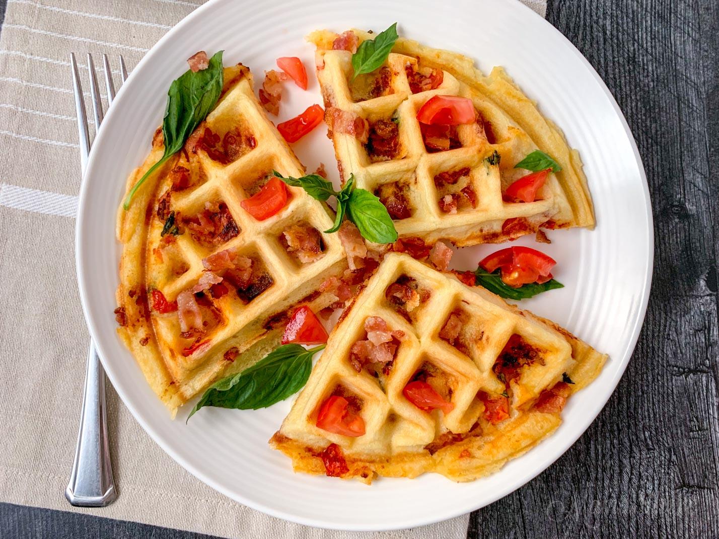 Bacon tomato gluten-free stuffed waffles with basil leaves.