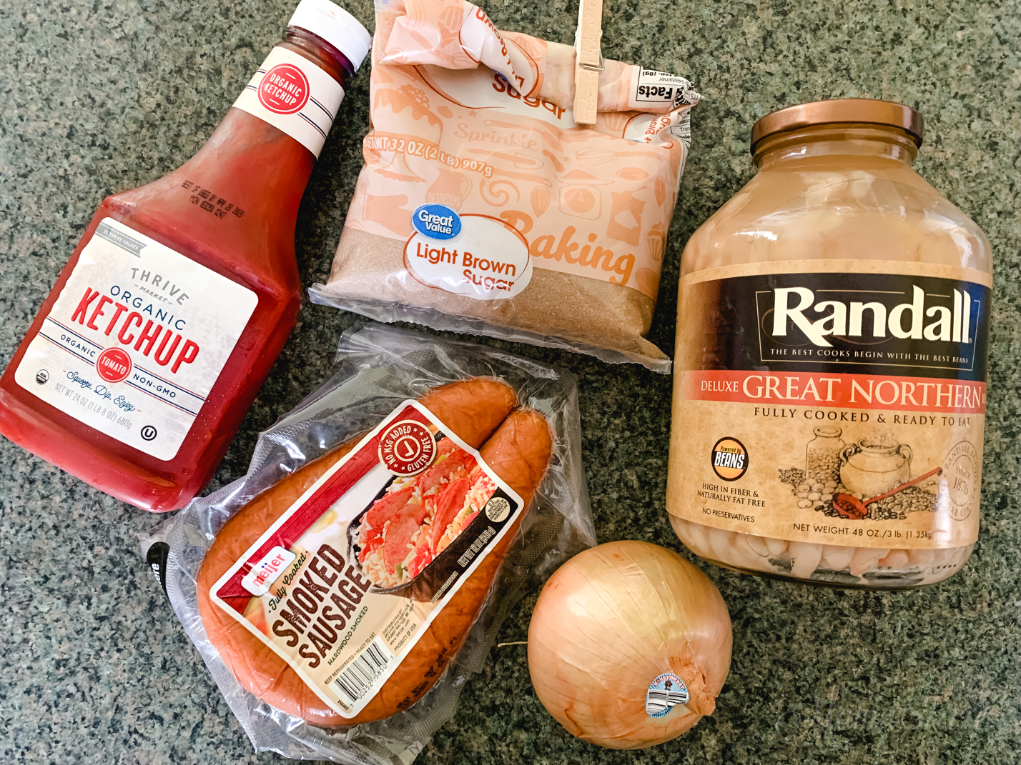 Ingredients for baked beans - brown sugar, great northern beans, onion, smoked sausage, and ketchup.