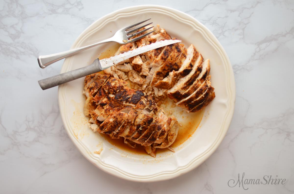 A white plate with two baked chicken breasts sliced up.