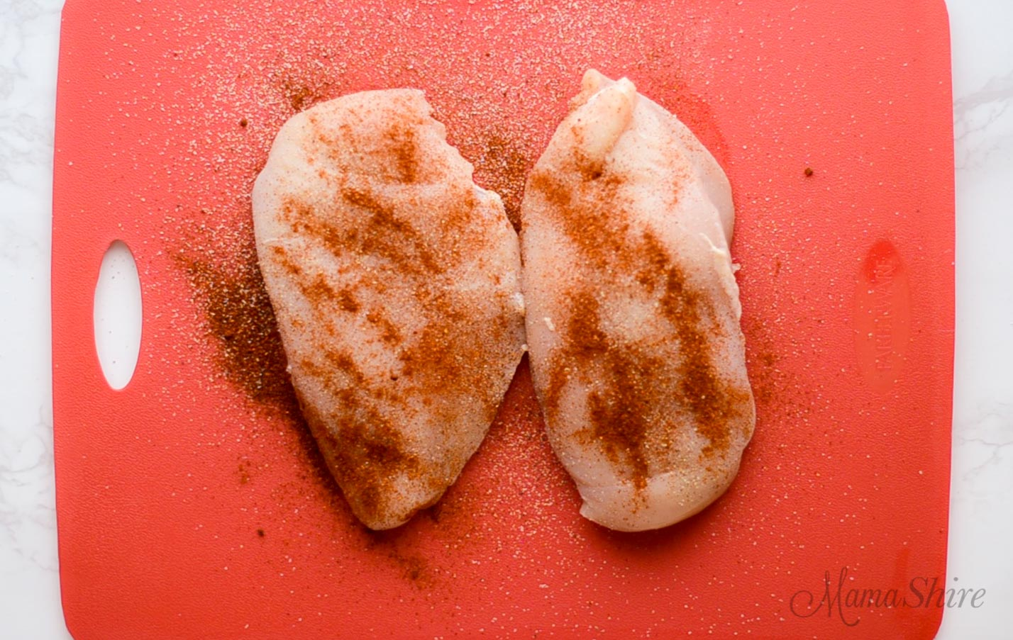 Two chicken breasts with seasoning ready to bake.