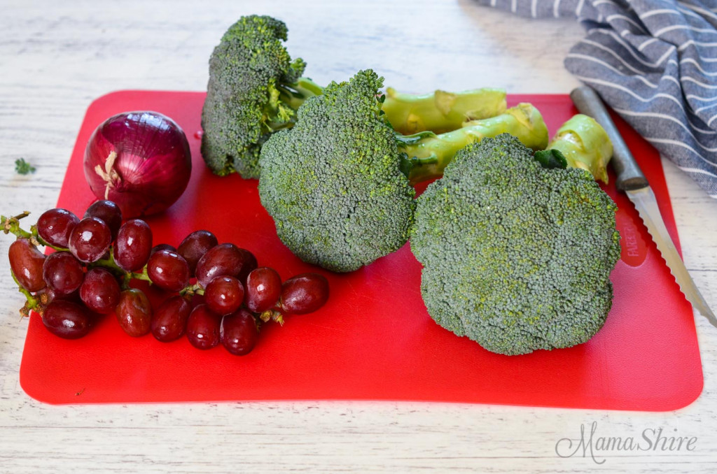 A red cutting board with broccoli, red grapes, and red onion.