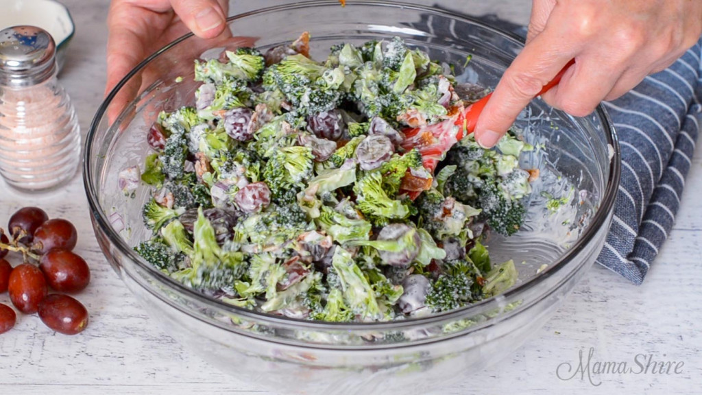 A clear mixing bowl with broccoli, bacon, grapes, red onions, and mayo getting all stirred together.