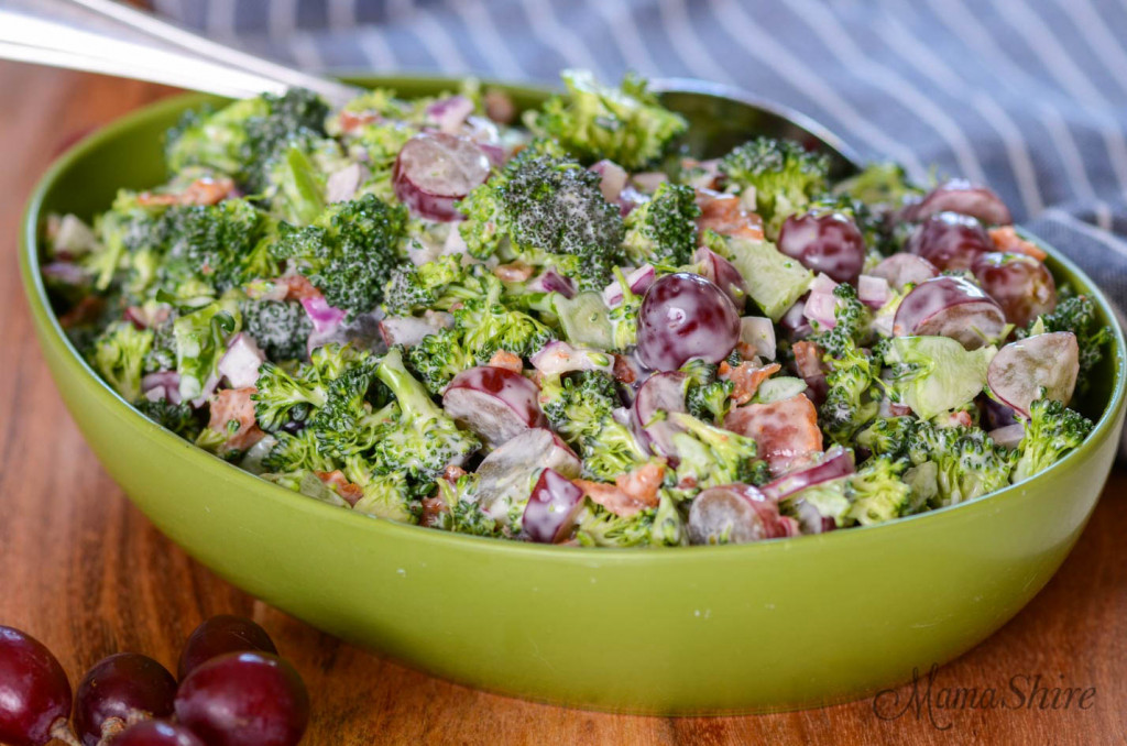 A serving bowl full of gluten-free broccoli salad with grapes.