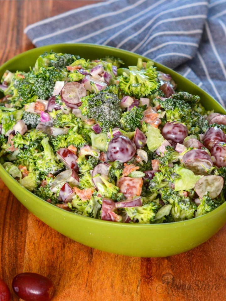 A green serving bowl filled with delicious broccoli salad with grapes and bacon.
