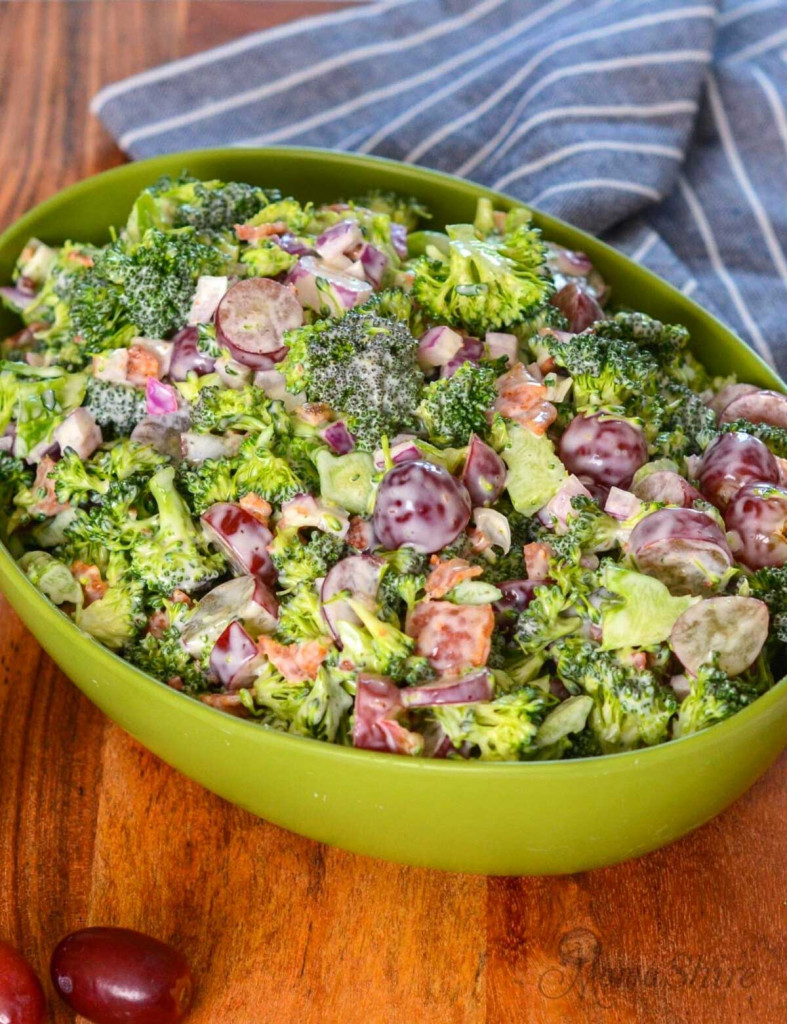 A green serving bowl filled with delicious broccoli salad with grapes.
