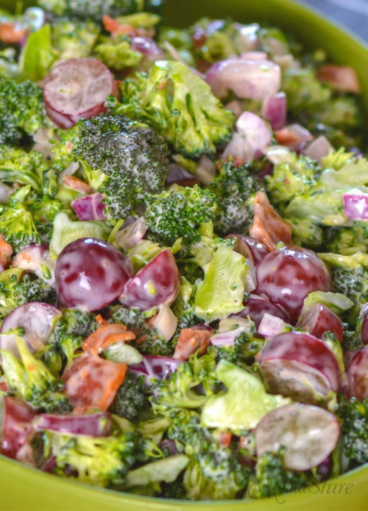 Up close picture of salad with grapes, broccoli, bacon, and red onion.
