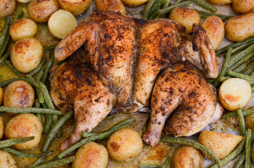 A whole chicken that has been cut and spread out like a butterfly and baked with veggies.