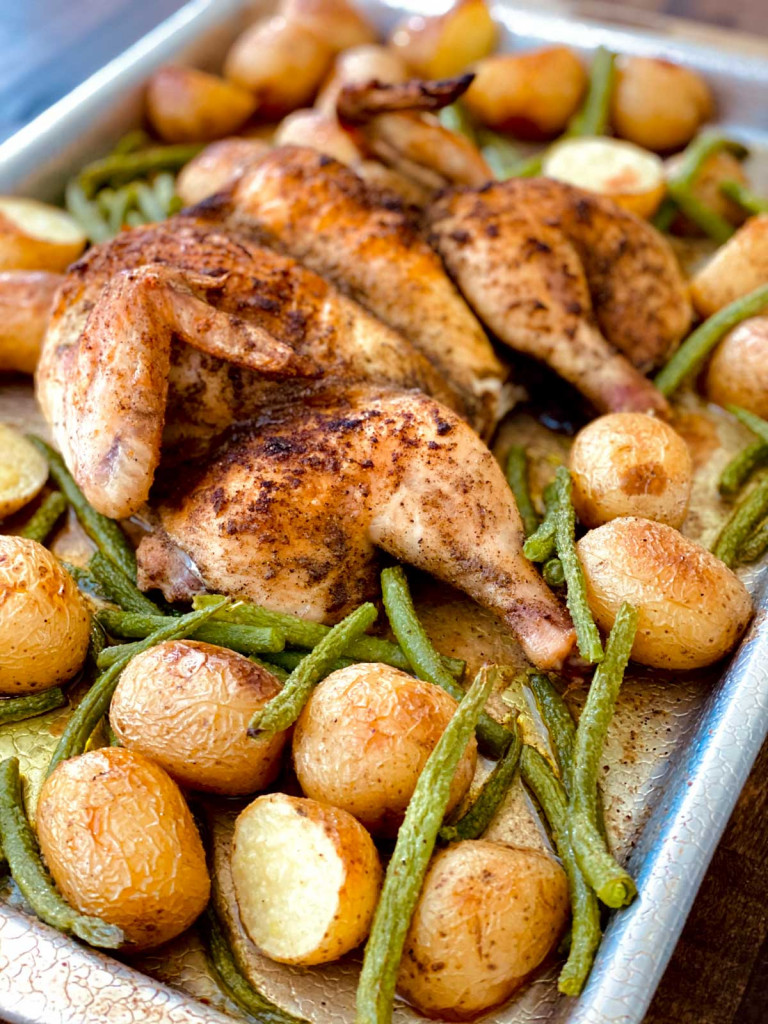 Potatoes, green beans, and a chicken that has been baked together.