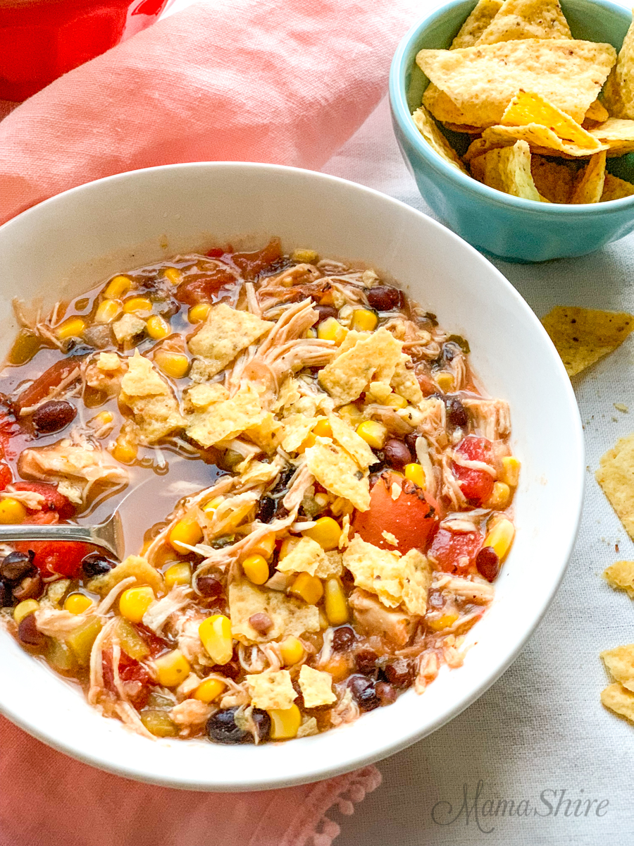 A bowl of chicken taco soup with salsa verde and sprinkled with tortilla chips.