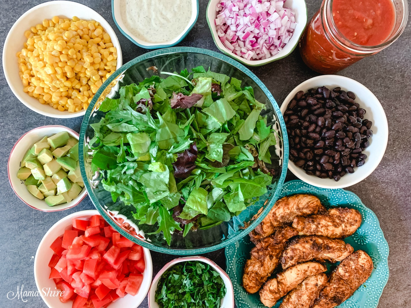 Ingredients for a healthy taco salad made with chicken, corn, tomatoes, black beans, avocados, cilantro, and red onions.