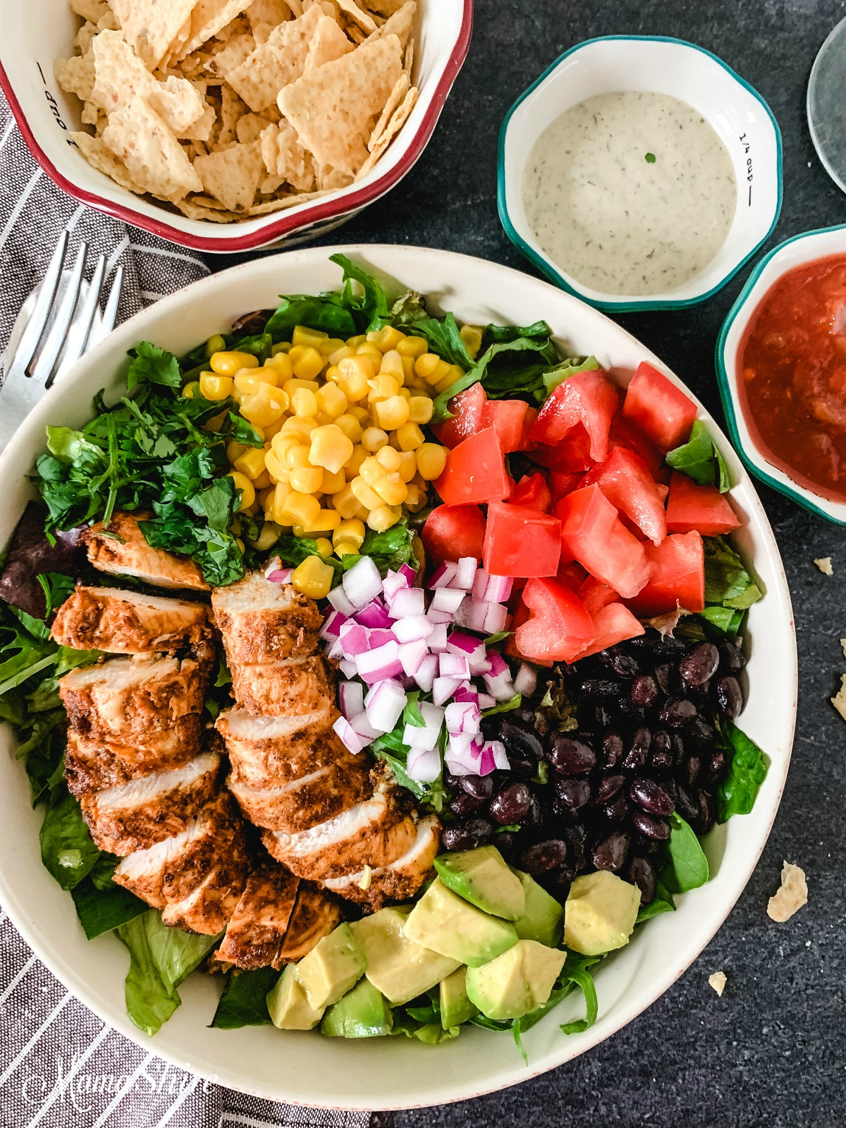 A colorful platter of taco salad with chicken made with black beans and corn.