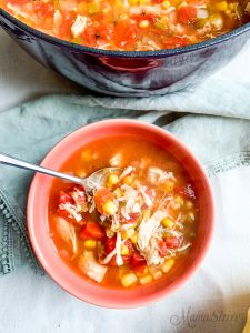 Tasty and satisfying chicken tortilla soup in a lovely coral bowl.