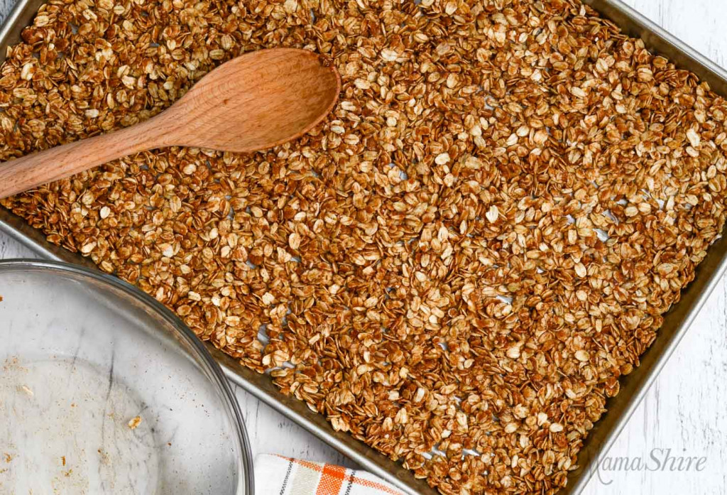 The granola mix all spread out in a baking pan ready to be baked.