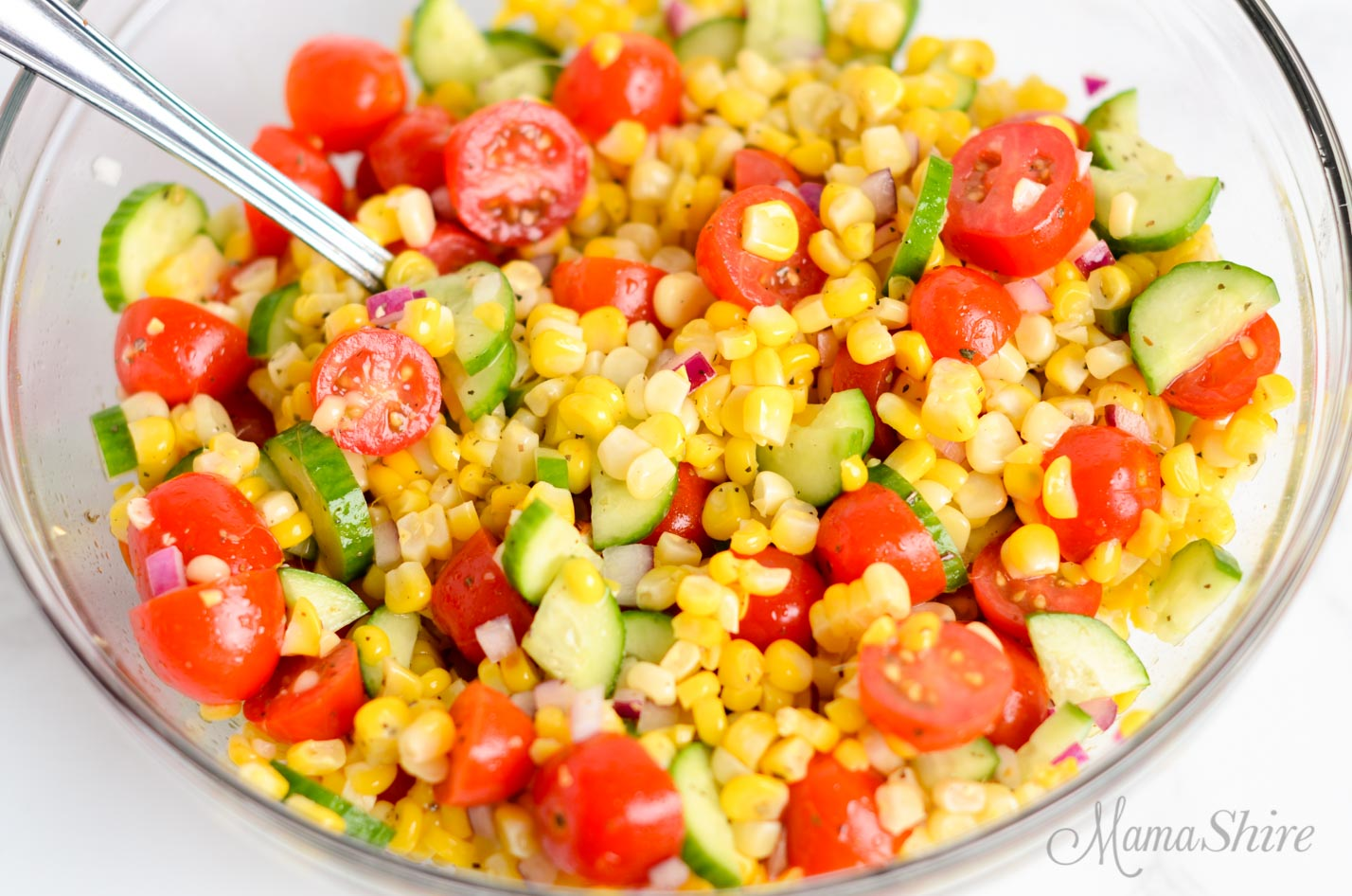 A serving bowl with corn salad that's naturally gluten-free with mini cucumbers and tomatoes.