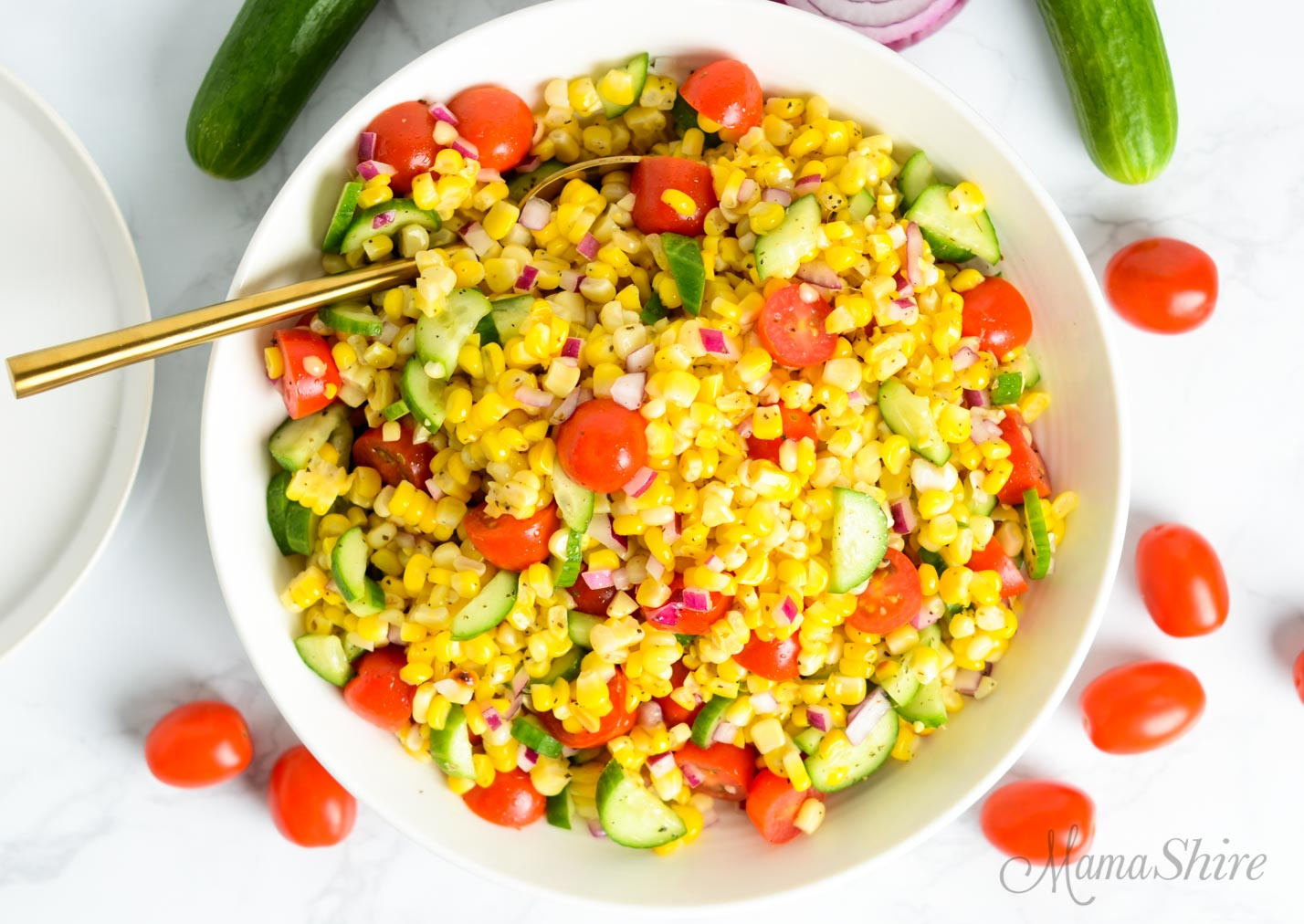 A serving bowl of easy corn salad with mini cucumbers, grape tomatoes, and red onions.