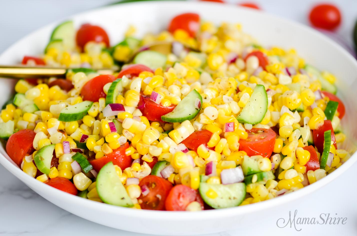Corn salad made with mini cucumbers and tomatoes.