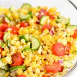 Corn salad that has cucumbers and tomatoes.