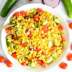 A white serving bowl with corn salad.