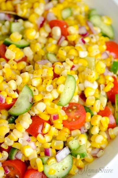 A closeup of a corn, cucumber, tomato, and red onion salad