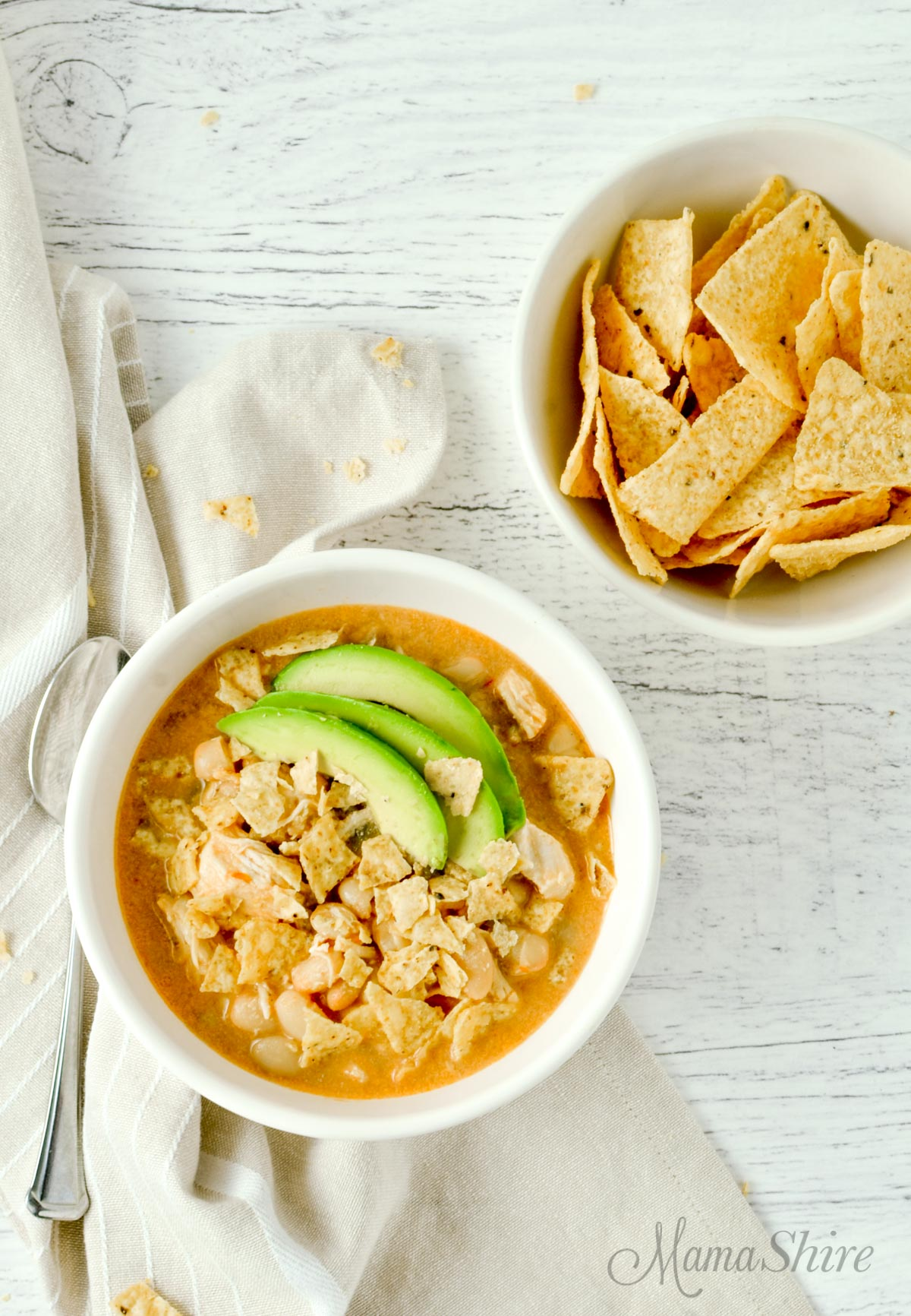 A bowl of white chicken chili made with tortilla chips on the side.