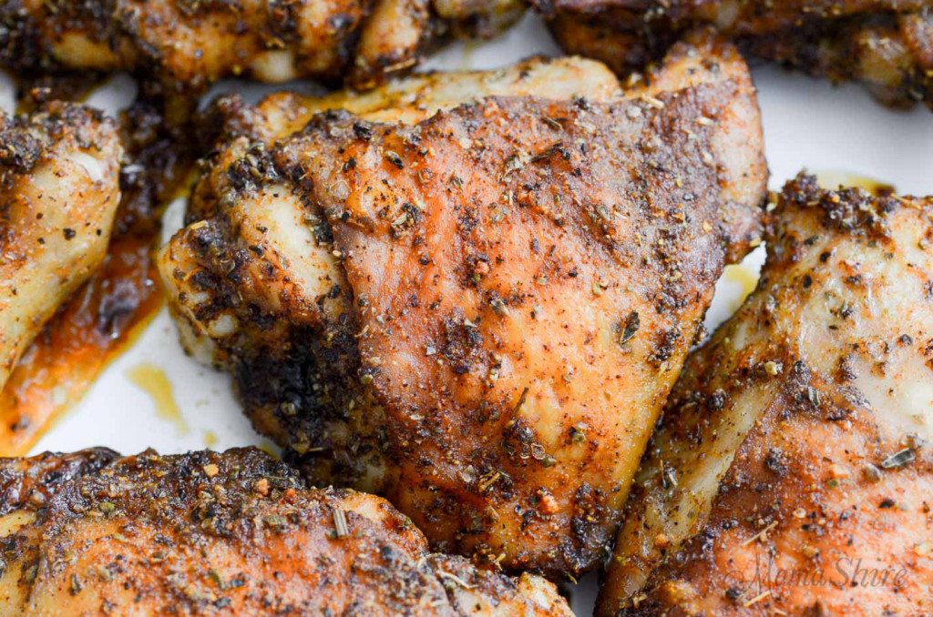 A closeup of a crispy baked chicken thighs and legs.