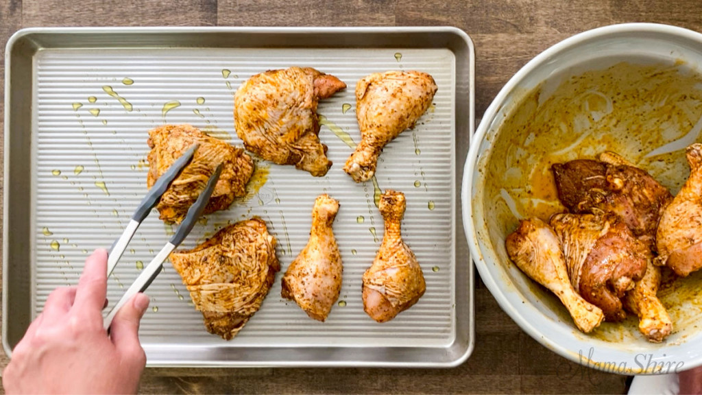 Placing coated chicken thighs and legs on a baking pan.