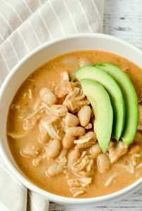 A white soup bowl with white bean chicken chili.