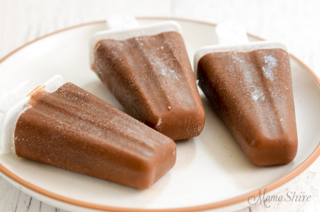 A sweet off-white plate with three fudgesicles made with a dairy-free recipe.