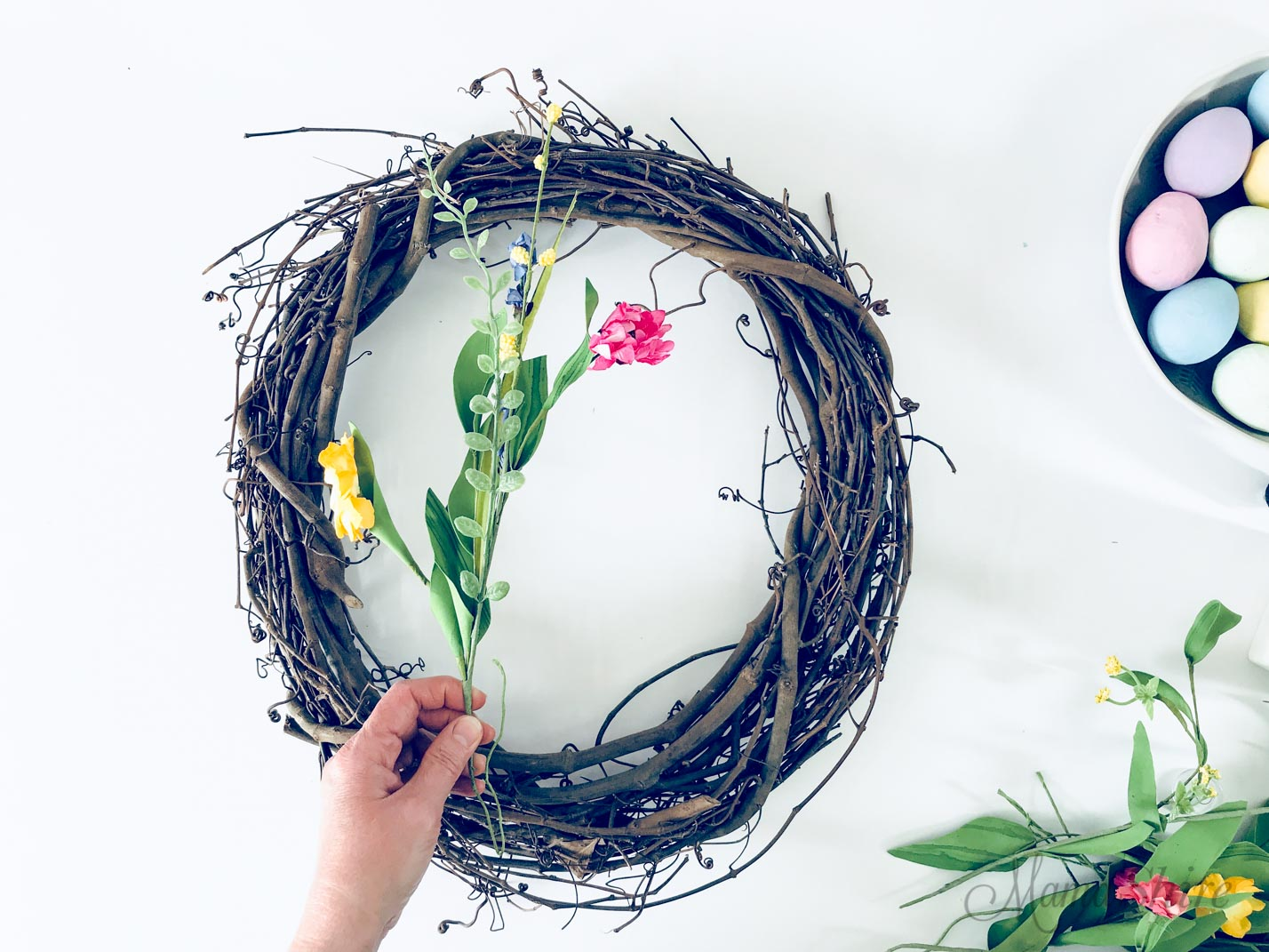 Grapevine wreath with a sprig of flowers.