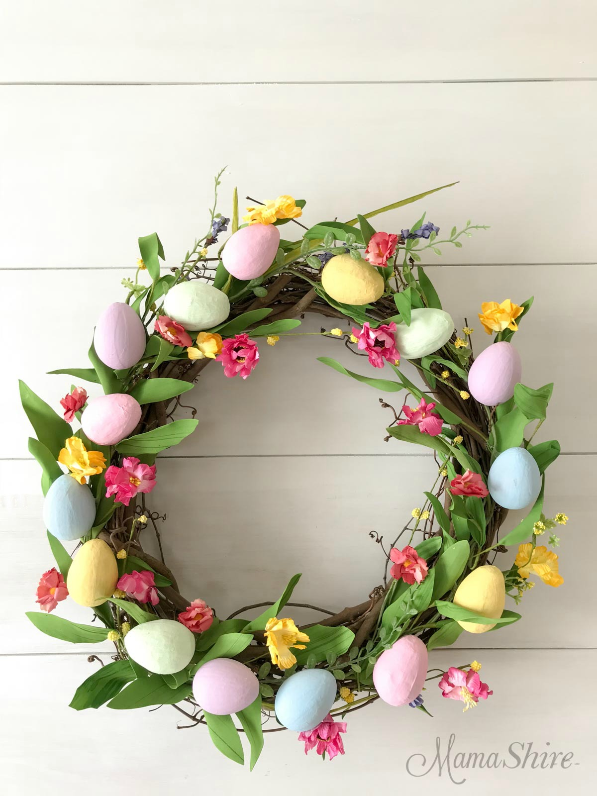 Pretty spring wreath with flowers and painted paper mache eggs.