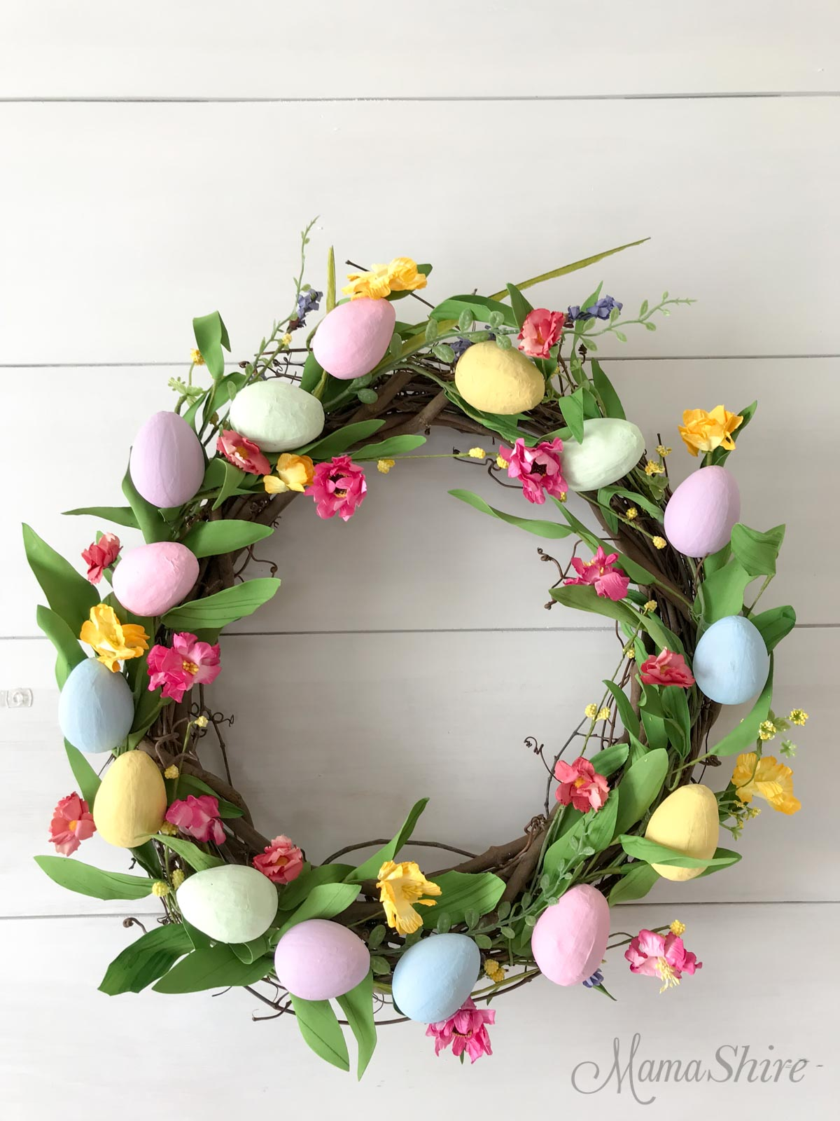 Easter Egg Wreath with flower garland and painted paper mache eggs.