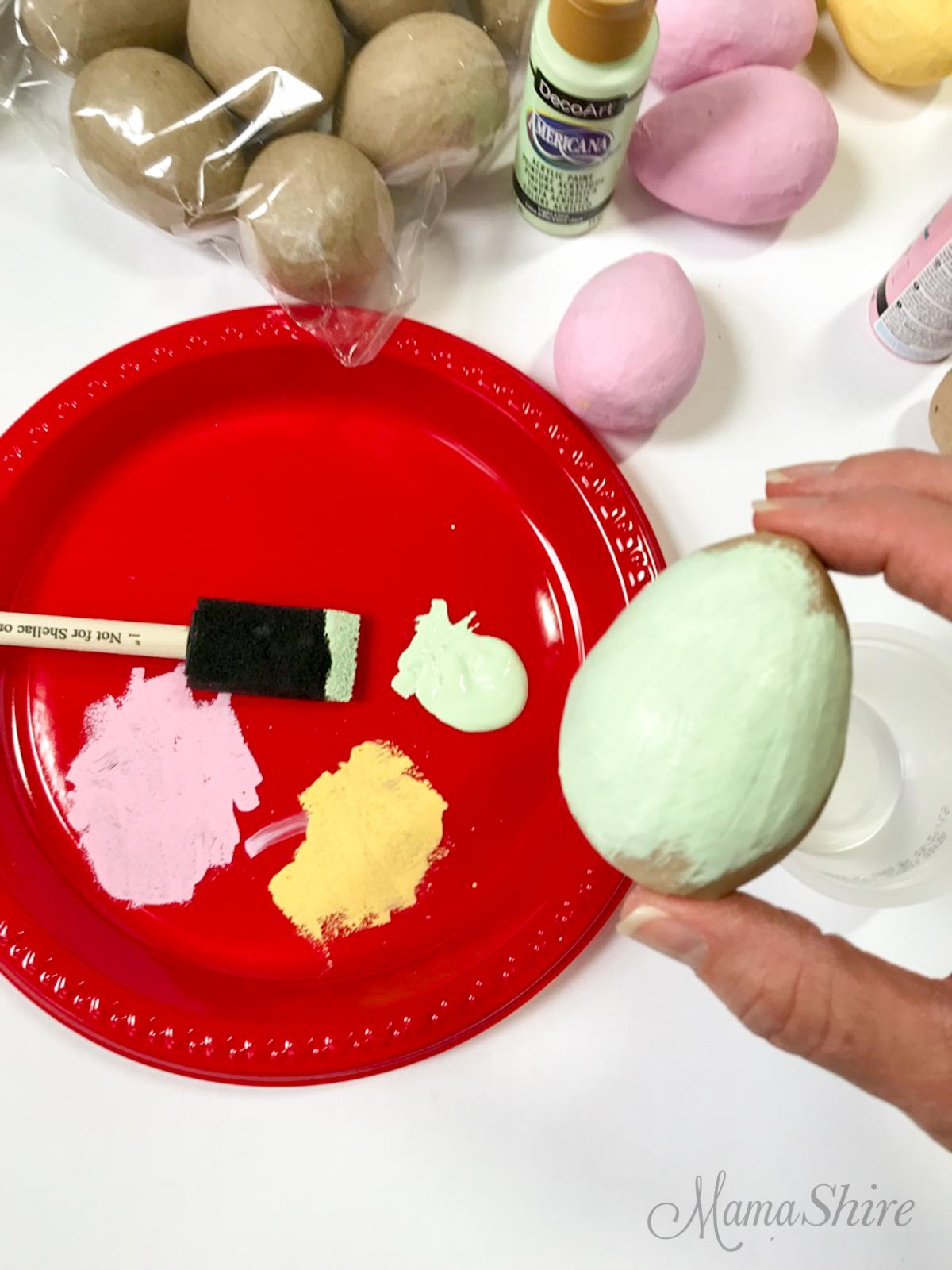 Painting a paper mache egg.
