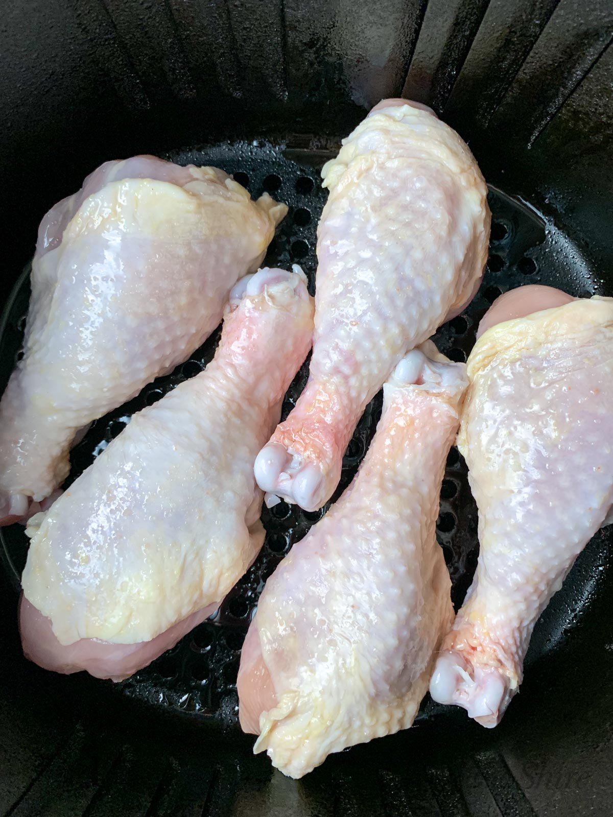 Raw chicken legs in an air fryer basket ready to be cooked.