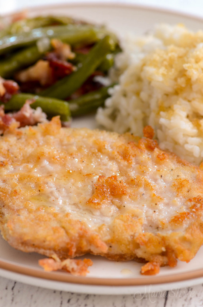A gluten-free pan-fried pork chop on a dinner plate with sweet rice and green beans.