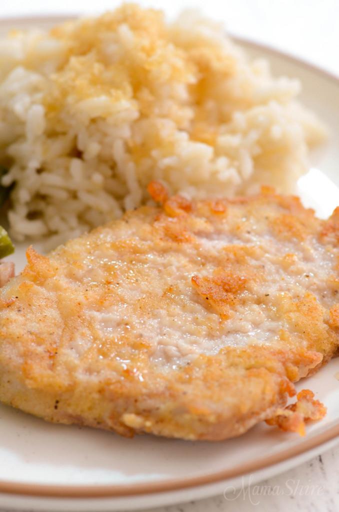 A close-up of a thin pan-fried pork chop made with gluten-free flour.