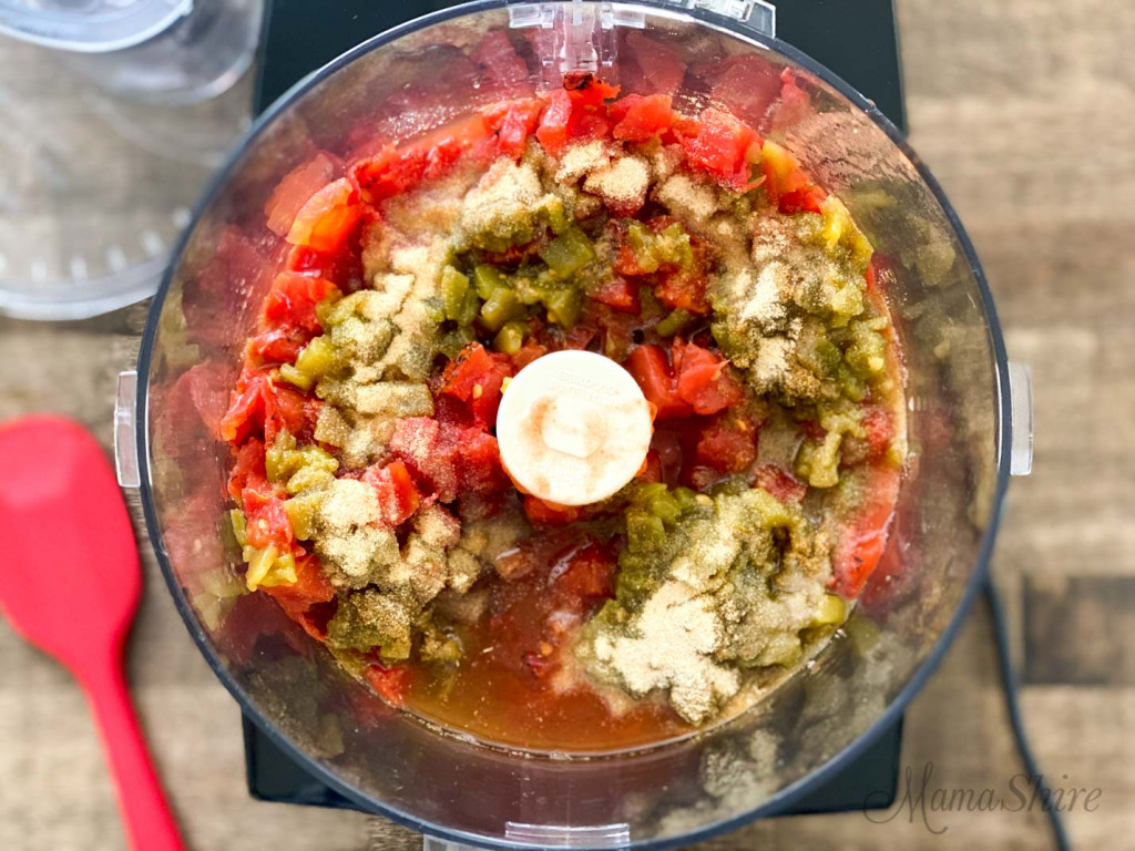 Tomatoes, chopped chiles, and seasonings for peach salsa in a food processor.