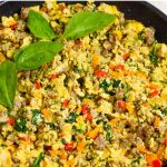A skillet with a hearty breakfast of sausage, eggs, peppers and spinach.