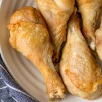 Easy air fryer chicken legs with crispy skin on a creamy white serving plate. No breading and gluten-free.