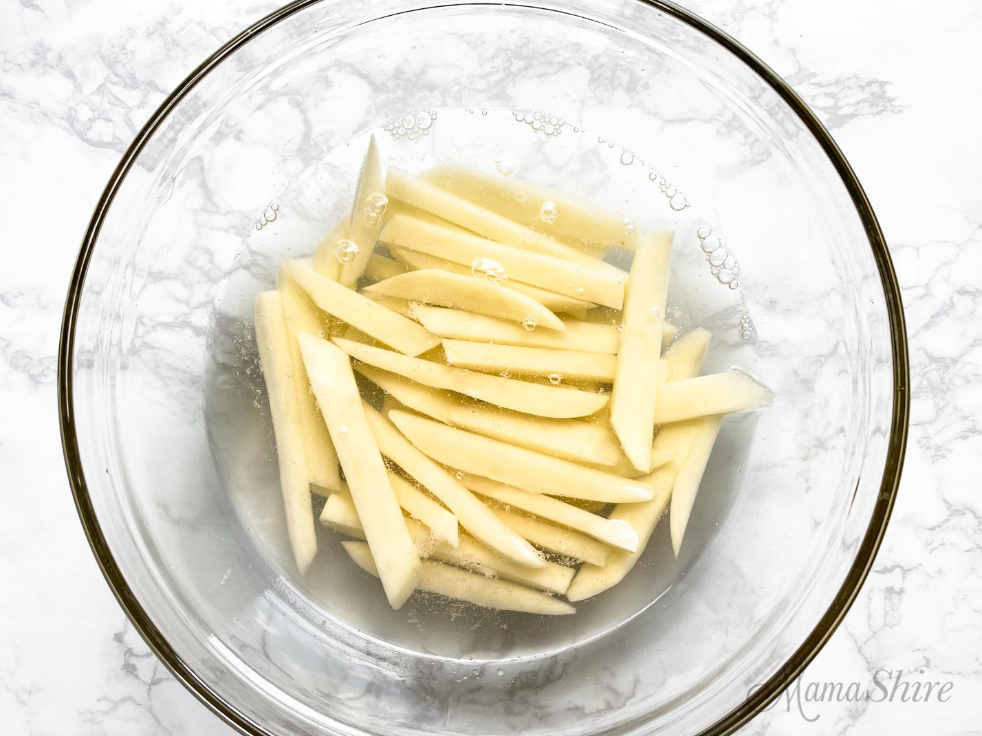 French fries soaking in salt water to remove the starchiness of the potatoes.